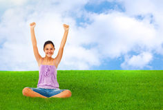 Sitting teenage girl on grass while rejoices with arms up. Royalty Free Stock Image