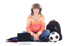 Sitting teenage girl listening music in headphones isolated on w Stock Image