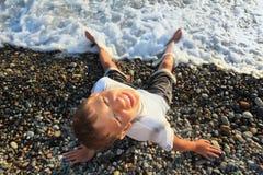 Sitting teenager boy looking upwards on seacoast Royalty Free Stock Photos
