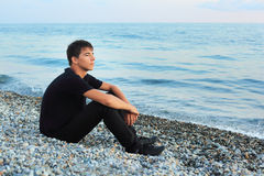 Sitting teenager boy on stone seacoast Stock Photo