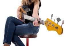 Sitting teenager playing on bass guitar Stock Image