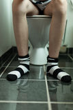 Sitting on a toilet Royalty Free Stock Images