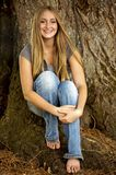 Sitting by the Tree. Beautiful blond teen model with hair blowing in the wind sitting by a tree royalty free stock photography