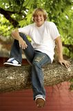 Sitting in a Tree. Young blond teenage boy sitting in a tall tree royalty free stock image