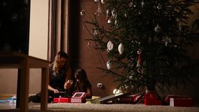 Sitting under a Christmas tree on the eve of Christmas, my mother gave her daughter a gift and a girl unpacked tied up. Gift ribbons. Camera movement stock video footage