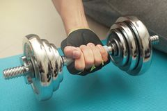 Sitting and using his right hand lifting weights at the shiny st. Eel,heavy steel dumbbell, Blue cloth on the floor exercise Stock Photography