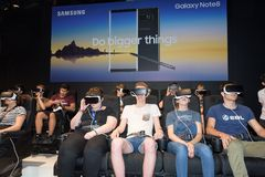 Sitting visitors watching a game by a virtual reality headset stock photos