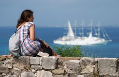 Sitting On A Wall. The girl sitting on St Louis fort wall in Marigot town with cruise liner in a background  (St.Martin island Stock Photos
