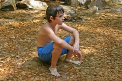 Sitting in the water. Boy sitting on stones in the water Stock Photos