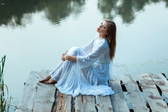 Sitting on the wharf of a beautiful girl. Royalty Free Stock Photo