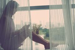Sitting on window-sill. Young woman sitting on window-sill and listening to the music stock image