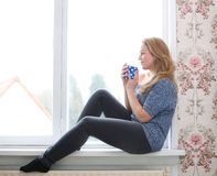 Sitting on windowsill with a  cup of tea Royalty Free Stock Photos