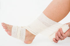 Sitting woman banding her ankle Stock Photo