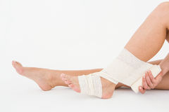 Sitting woman banding her ankle Stock Image