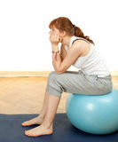 Sitting woman on big blue ball Royalty Free Stock Photography