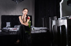 Sitting Woman in Black Dress Holding Rose Flower Royalty Free Stock Images