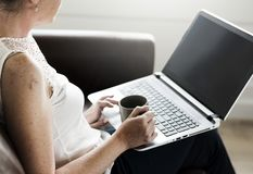 Sitting Woman on Brown Sofa With Laptop on Her Lap While Holding Mug royalty free stock photography