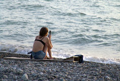Sitting woman with cellphone. Against a sea background Royalty Free Stock Photos