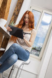 Sitting Woman with a Glass of Drink and a Tablet Stock Photo