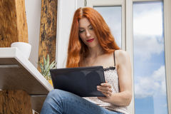 Sitting Woman with a Glass of Drink and a Tablet Royalty Free Stock Image