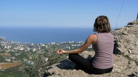 Sitting woman in lotus position practicing yoga moves. Cliff top with the cross. View from the back to the sitting woman in lotus position practicing yoga moves stock video footage