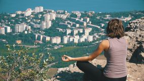 Sitting woman in lotus position practicing yoga moves. Cliff top with the cross. View from the back to the sitting woman in lotus position practicing yoga moves stock video
