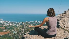 Sitting woman in lotus position practicing yoga moves. Cliff top with the cross. View from the back to the sitting woman in lotus position practicing yoga moves stock footage