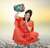 Sitting woman in orange sari holding turban Royalty Free Stock Photography