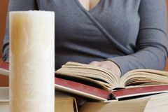 Sitting woman reading a book with a candle. Sitting woman reading a book with a standing candle Stock Photo
