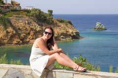 Sitting woman at sea coast on Crete island Stock Photo