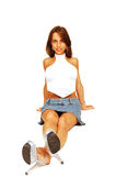 Sitting woman in short skirt. An very fit woman in a short skirt and white top sitting on the floor in an Royalty Free Stock Photos
