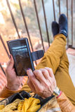 Sitting woman with smartphone on balcony Stock Photography