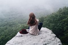 Sitting Woman Wearing Checked Shirt on Rock Cliff over Green Trees Royalty Free Stock Photo