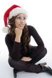 Sitting woman wearing christmas hat. On an isolated background Royalty Free Stock Photography