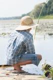 Sitting on wooden bridge shoeless fisherman with Royalty Free Stock Image