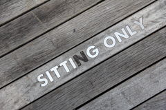 Sitting only words written on wooden board. Wooden board signed sitting only Royalty Free Stock Photography