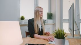 Woman showing thumbs down in office. Sitting at workplace young blond female in business suit looking at camera and stock video