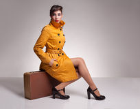 Sitting yellowcoat. Beautiful brunette model with her hand in her pocket posing with her yellow overcoat while sitting on her retro suitcase on grey background Stock Photo