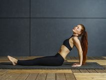 Sitting yoga with a beautiful redhead woman. Photo of a beautiful redhead doing yoga on a floor mat in a gym Royalty Free Stock Images