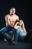 Sitting young beautiful couple. isolated shot. Portrait of a young couple sitting. erotic love picture. couple dressed in a casual style, blue jeans. a man's Royalty Free Stock Image
