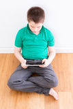 Sitting Young Boy Holding Tablet Leaning on Wall Royalty Free Stock Images