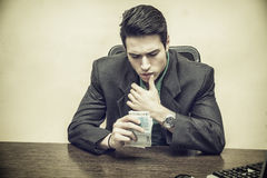 Sitting Young Businessman Counting Cash on Hand. Close up Serious Young Businessman, Sitting at his Worktable, Counting Cash on Hand Seriously Stock Photos