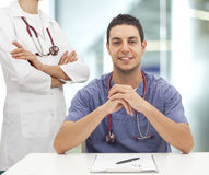 Sitting young doctor man and his nurse Stock Photography