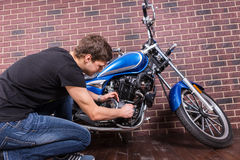 Sitting Young Guy Repairing his Motorcycle Stock Photos