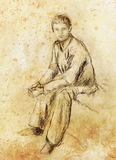 Sitting young man drawing, eye contact, paper background. Royalty Free Stock Photography