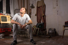 Sitting Young Man at Junked Room Looking Up Stock Images