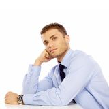 Sitting Young Salesman with Hand on Face Royalty Free Stock Photos