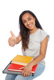 Sitting Young Woman with Books Showing Thumbs Up Royalty Free Stock Photography