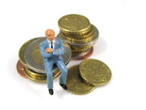 Sitting on your fortune. A man figurine sitting on his money stock image