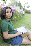 与计算机的女孩sittingon绿草在手中压片 免版税图库摄影